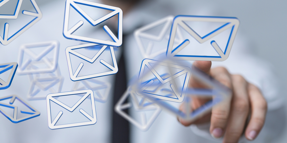 Man touching email icons floating in the air
