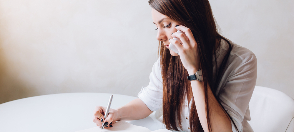 Young woman cold calling and taking notes