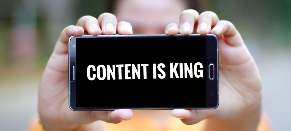 """Person holding a phone that displays the words """"Content is king"""""""