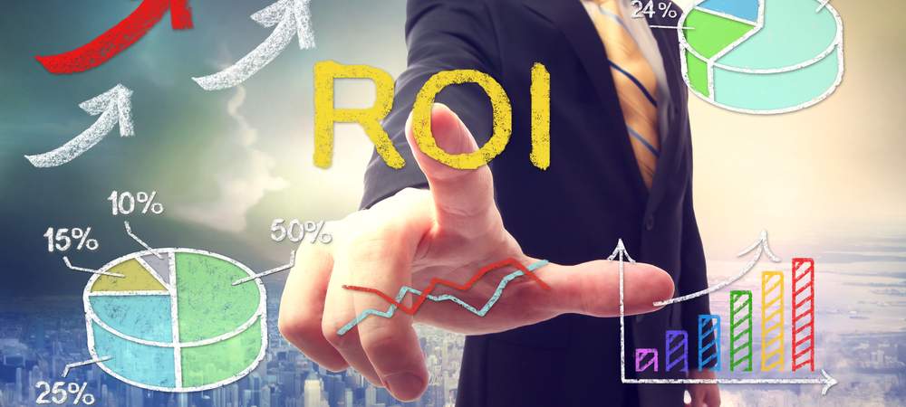 Man touching a drawing that says ROI and hard a chart pie next to it