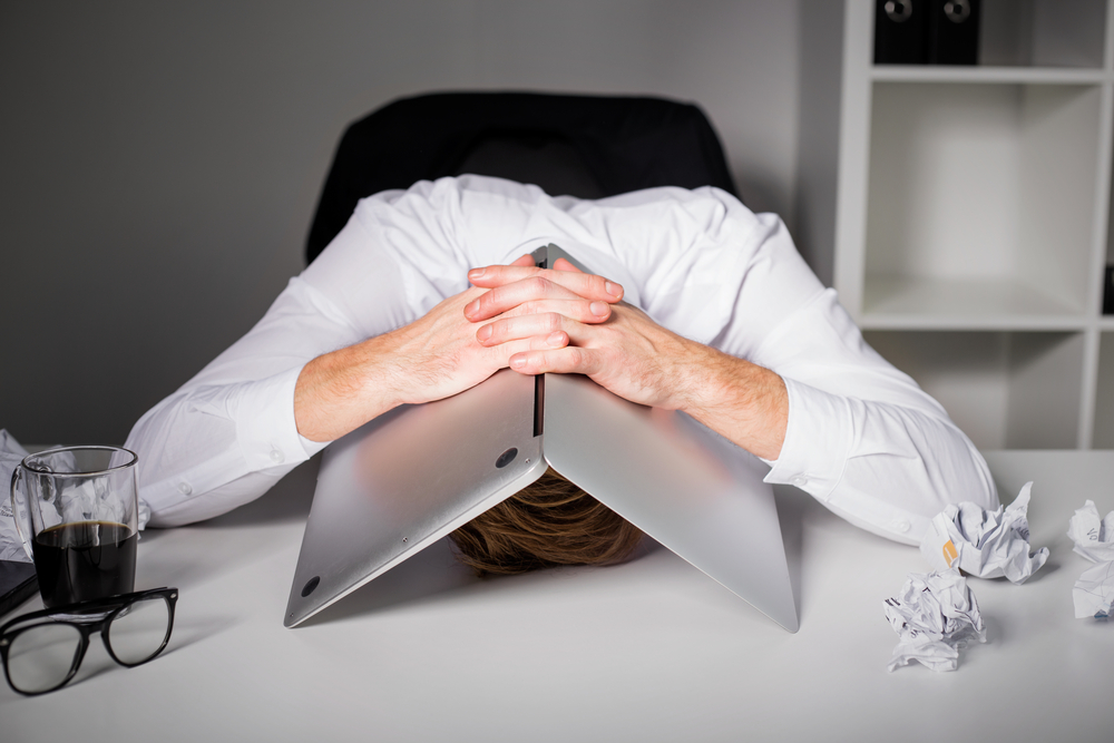 Stressed man holding his laptop over his head