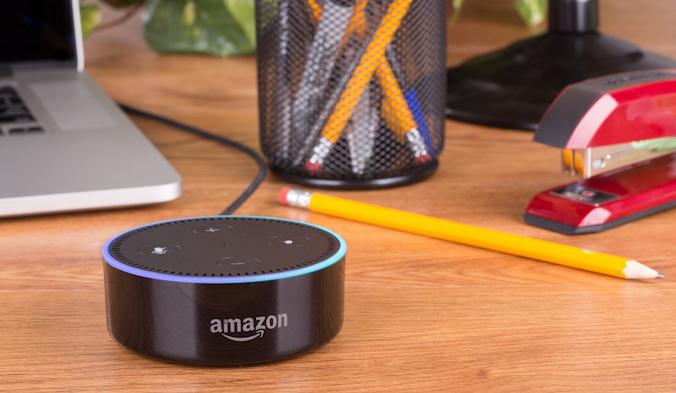 Amazon Alexa on a desk near business supplies and a laptop.