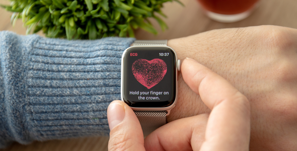 A person's wrist with a watch that displays their heartbeat