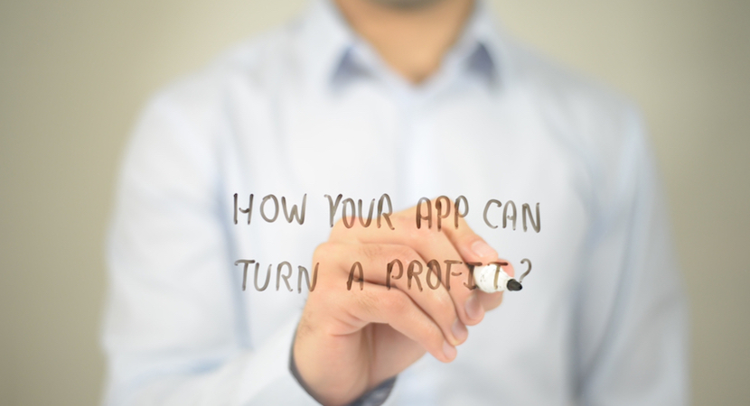 "Man writing the words ""How your app can turn a profit?"" on a board."