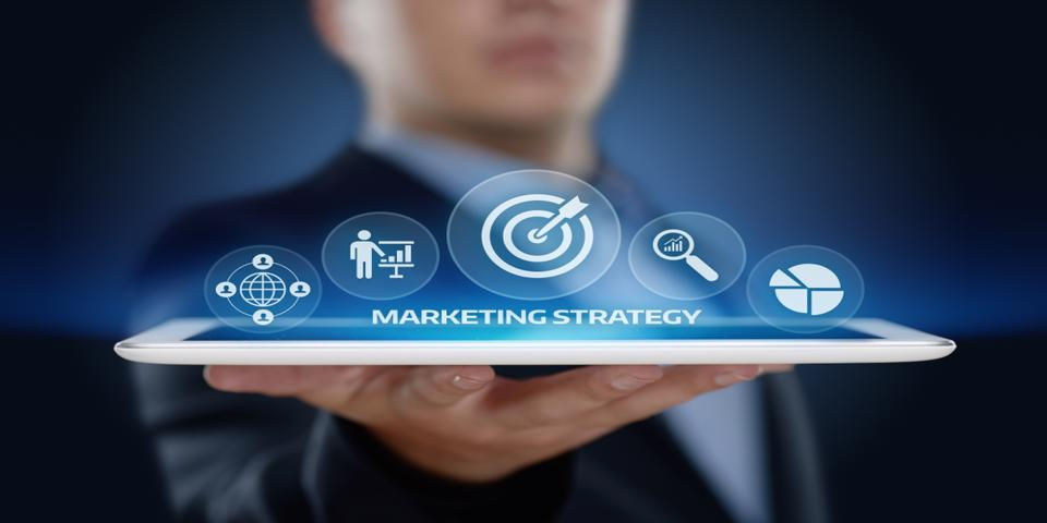 Man holding a tablet with marketing strategy icons